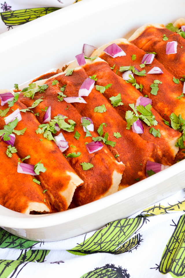 red enchiladas topped with onion and cilantro