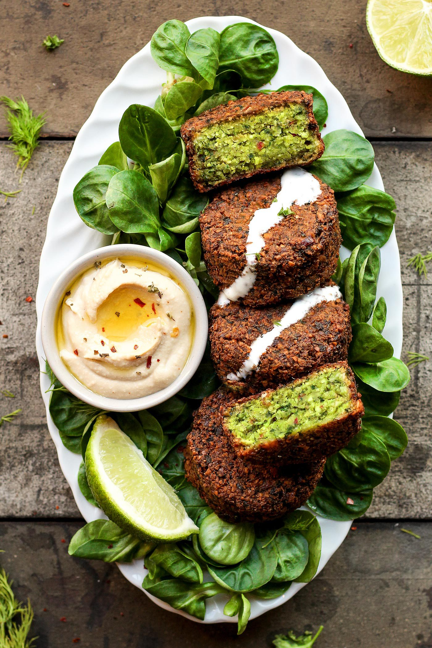 green falafel on plate with hummus